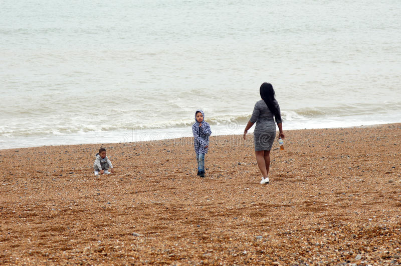 Mother with her kids on the beach royalty free stock image