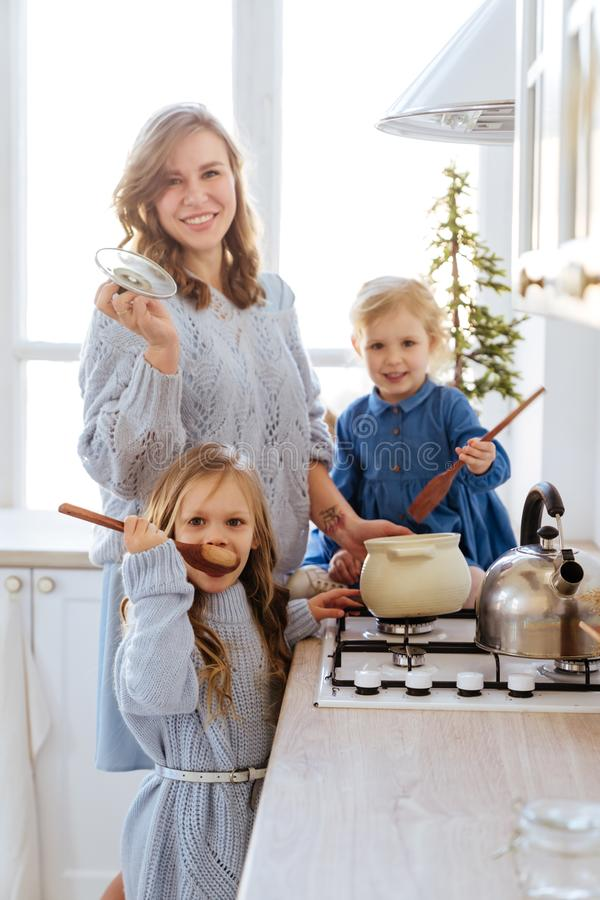 Mother with her kids cooking in the kitchen to xmas. Casual lifestyle photo series in real life interior royalty free stock images