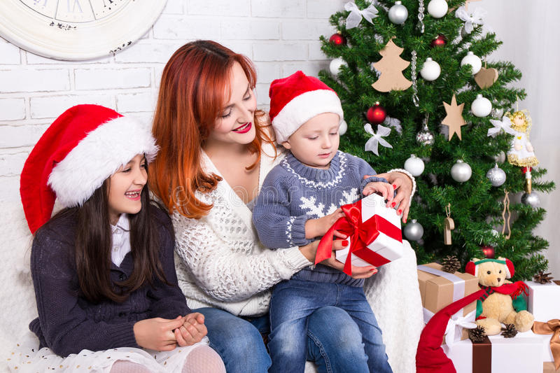 Mother and her kids with gifts and Christmas tree royalty free stock photography