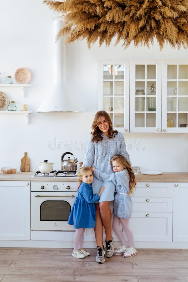 Mother with her kids in the kitchen to xmas. Casual lifestyle photo series in real life interior stock images