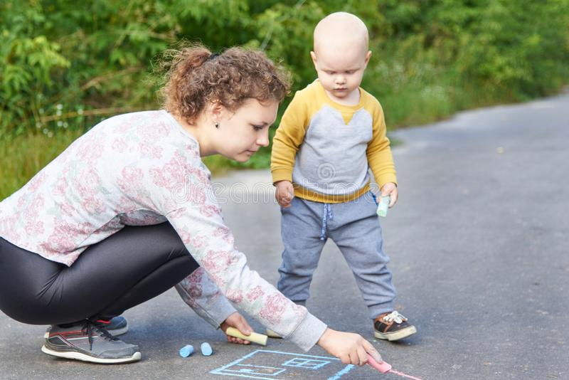 Mother with her little son draws a colorful chalk on asphalt on a summer day. Mom and child activity. Mother with her little cute son draws a colorful chalk on stock photography