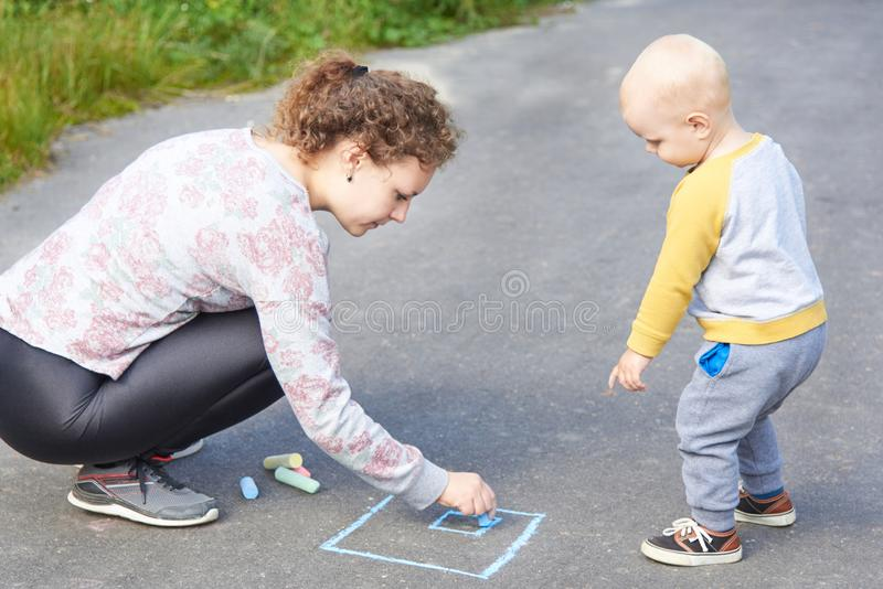 Mother with her little son draws a colorful chalk on asphalt on a summer day. Mom and child activity. Mother with her little cute son draws a colorful chalk on stock photos