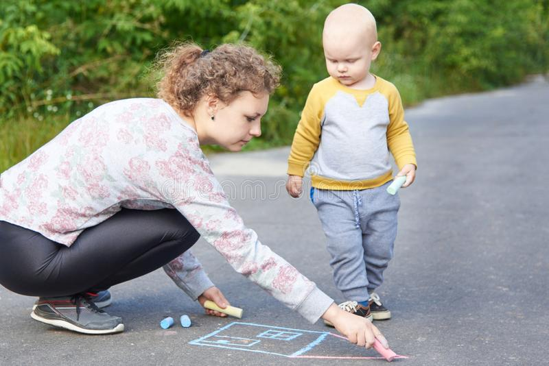 Mother with her little son draws a colorful chalk on asphalt on a summer day. Mom and child activity. Mother with her little cute son draws a colorful chalk on royalty free stock photos