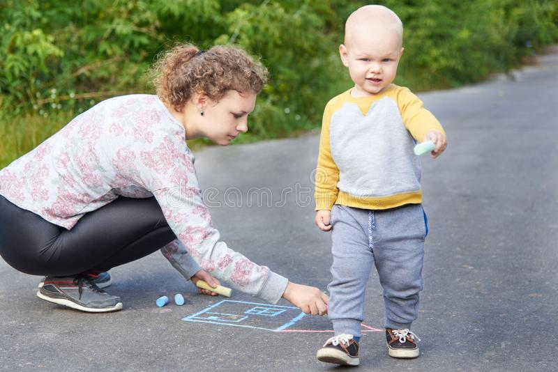 Mother with her little son draws a colorful chalk on asphalt on a summer day. Mom and child activity. Mother with her little cute son draws a colorful chalk on stock photo