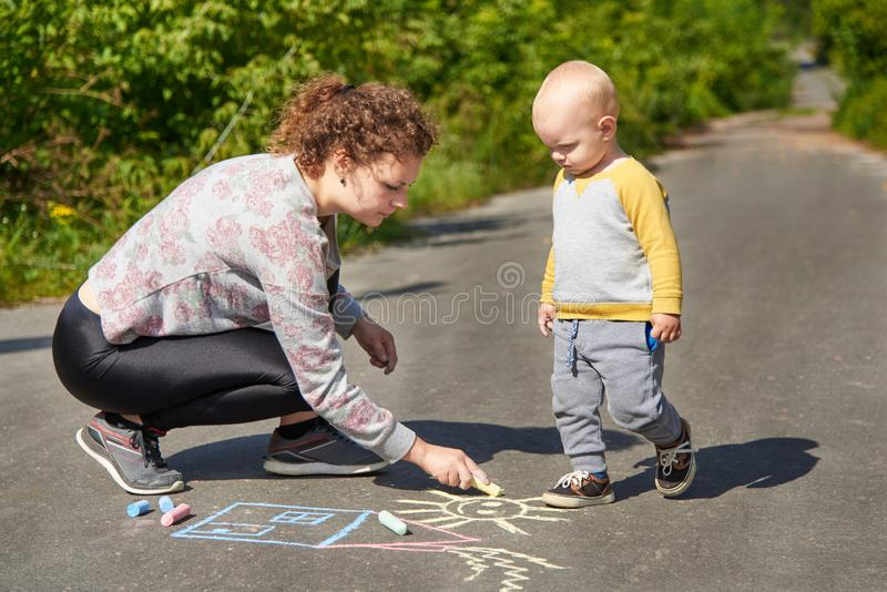 Mother with her little son draws a colorful chalk on asphalt on a summer day. Mom and child activity. Mother with her little cute son draws a colorful chalk on royalty free stock photo