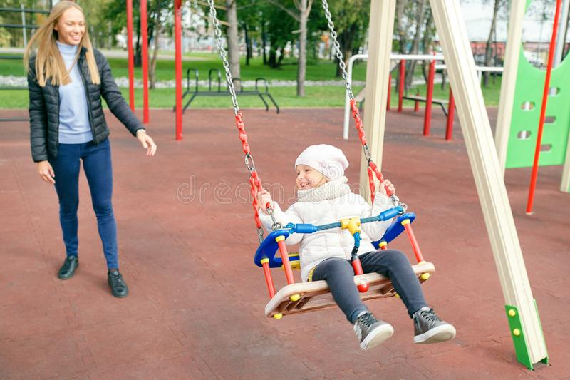 Mother and her little daughter at city autumn park, playground. royalty free stock image