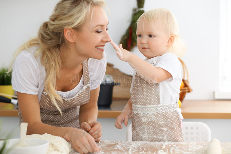 Mother and her little daughter cooking holiday pie or cookies for Mother`s day. Concept of happy family in the kitchen stock photography