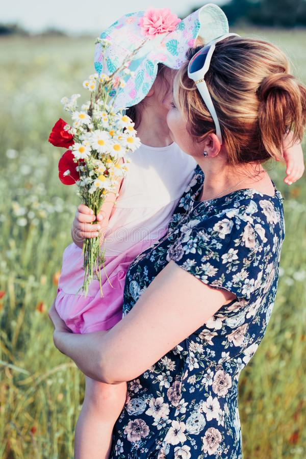 Mother and her little daughter in the field of wild flowers. Little girl picking the spring flowers for her mom for Mother`s Day in the meadow. Girl handing stock images