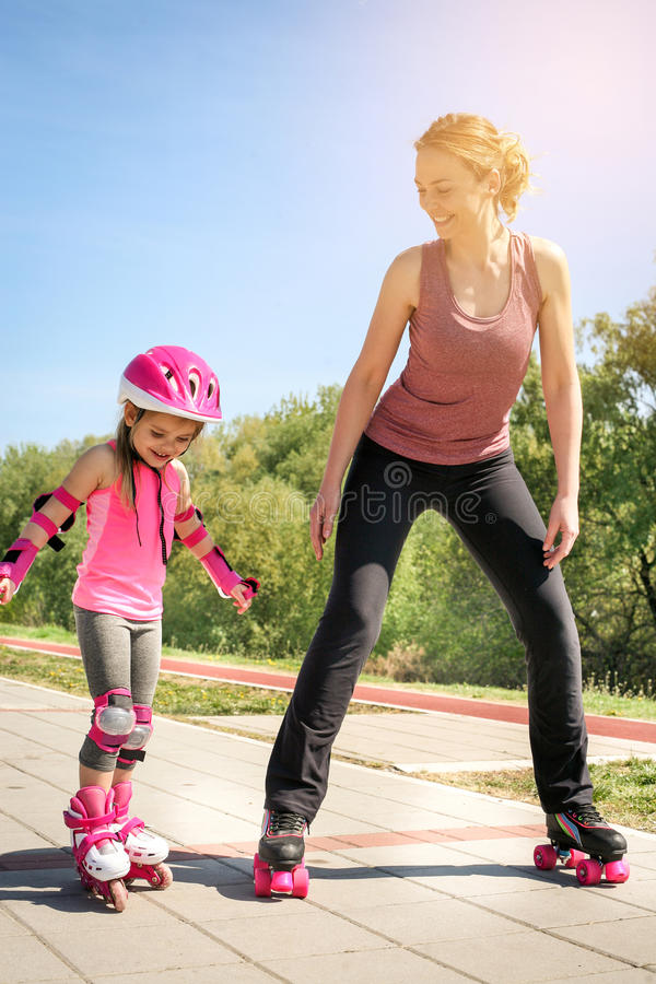 Mother and her little daughter inline skating on sidewalk. royalty free stock image