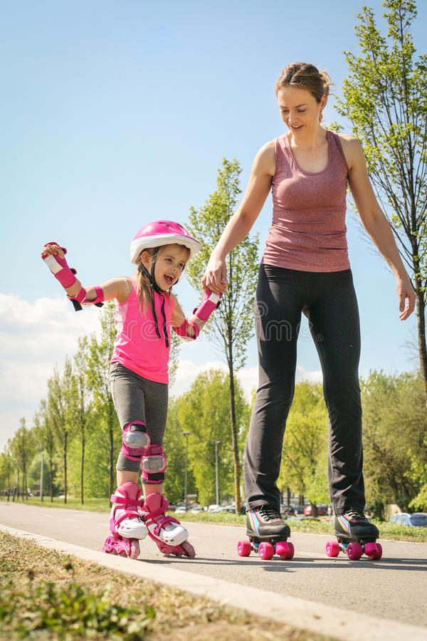 Mother and her little daughter inline skating on sidewalk. Mother and daughter enjoying in spring day royalty free stock images