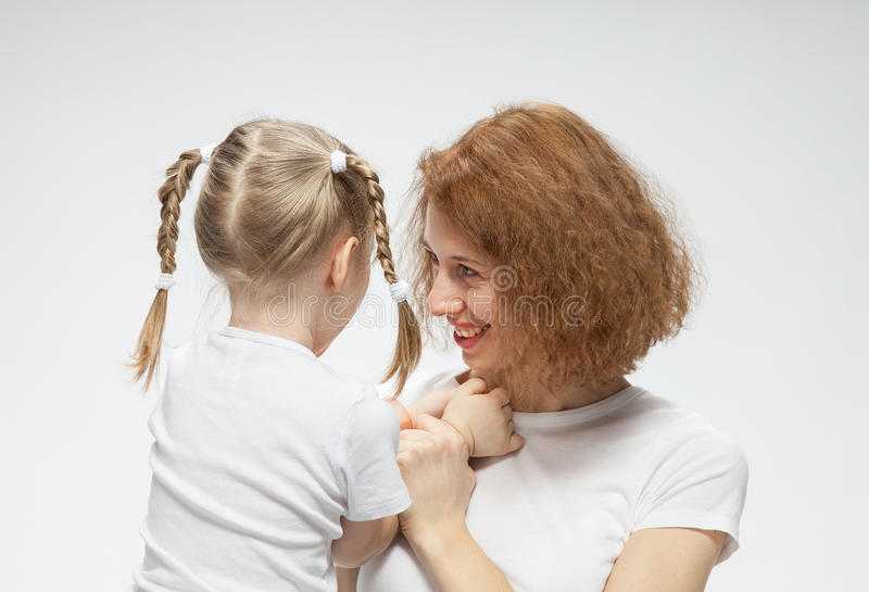 Mother and her little daughter playing. Neutral background royalty free stock photography