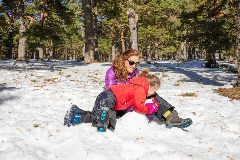 Mother and her little daughter playing on the snow stock photo
