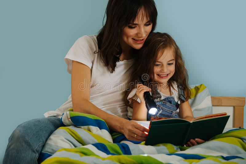 Mother and her little daughter are reading book in bed before going to sleep royalty free stock images