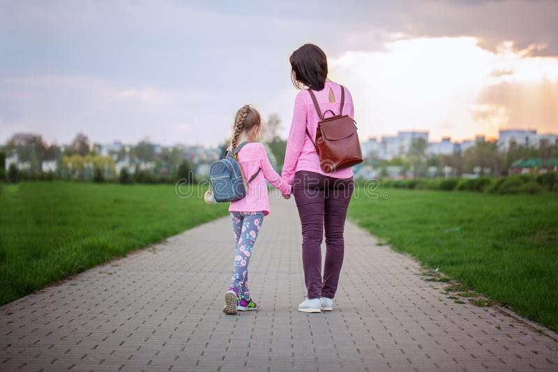 Mother and her little dauther with backpack walking in summer day. View from a back. royalty free stock image