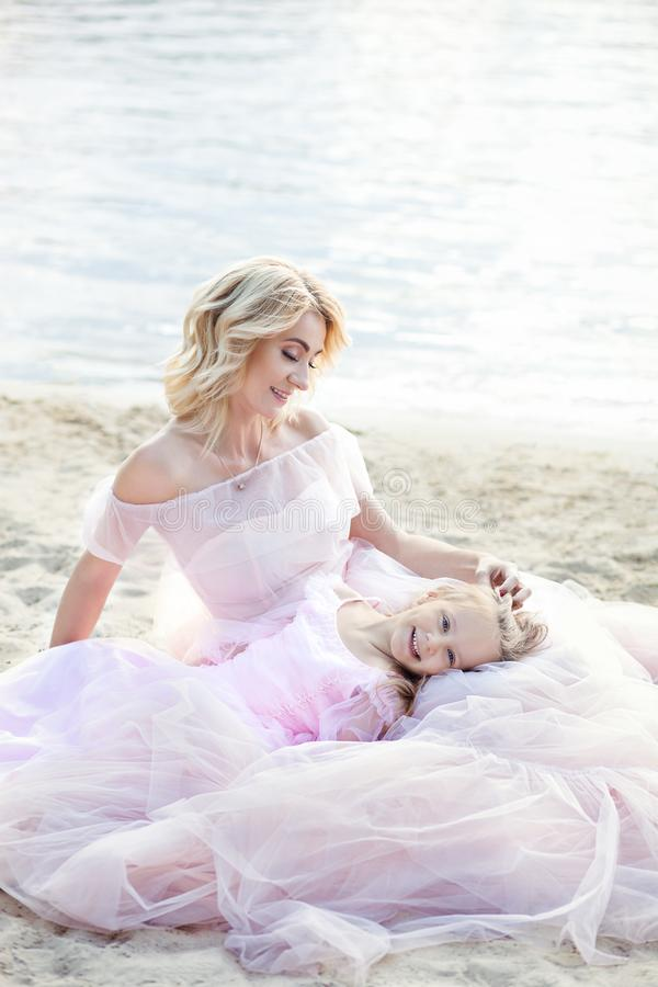 Mother and her little girl enjoying lake view and relaxing on the beach on a sunny day in beautiful dresses. A cheerful child and royalty free stock photo