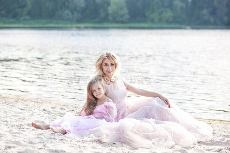 Mother and her little girl enjoying lake view and relaxing on the beach on a sunny day in beautiful dresses. Family lifestyle and stock photography