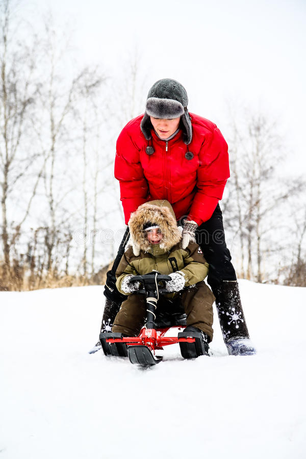 Mother and her little son enjoying a sledge ride in a snowy park royalty free stock photos