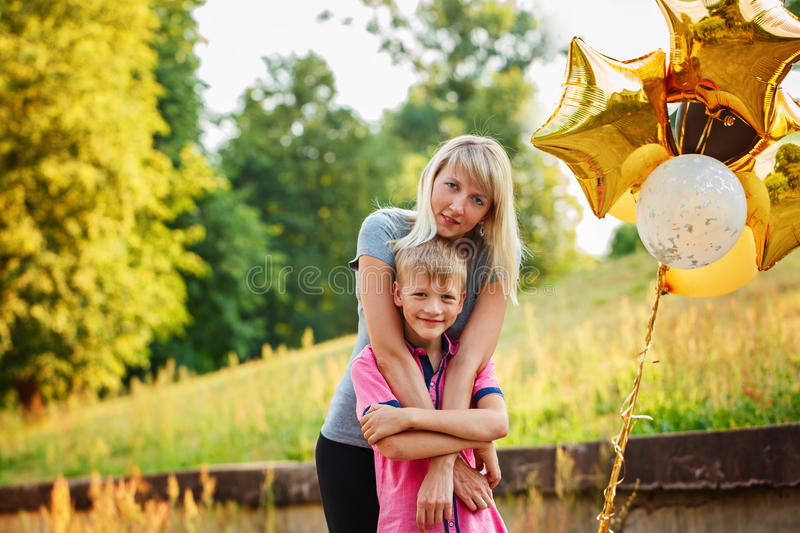 Mother and her little son with gold balloons in summer day. Happy family mom and kid hugging stock photos