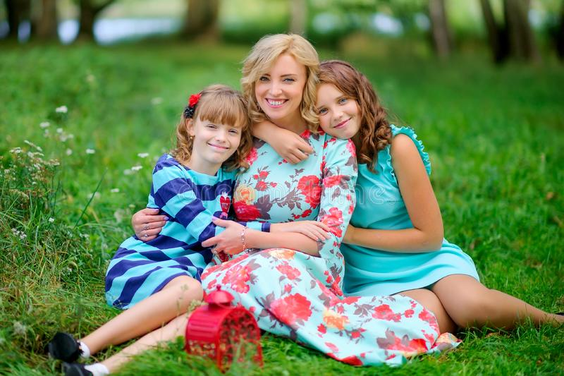 Mother with her lovely daughters in the park stock photography