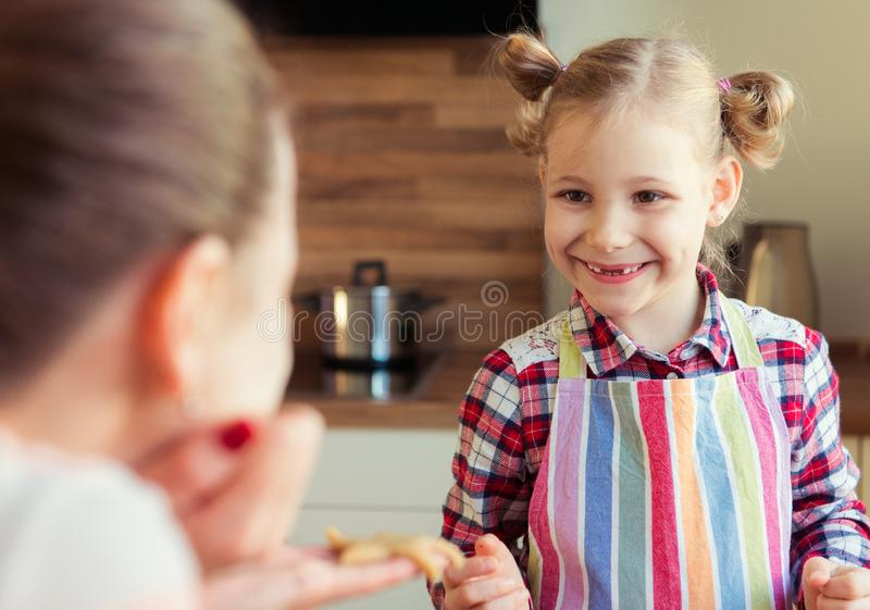 Mother and her pretty little doughter baking christmas ginger co. Okies in modern kitchen royalty free stock image