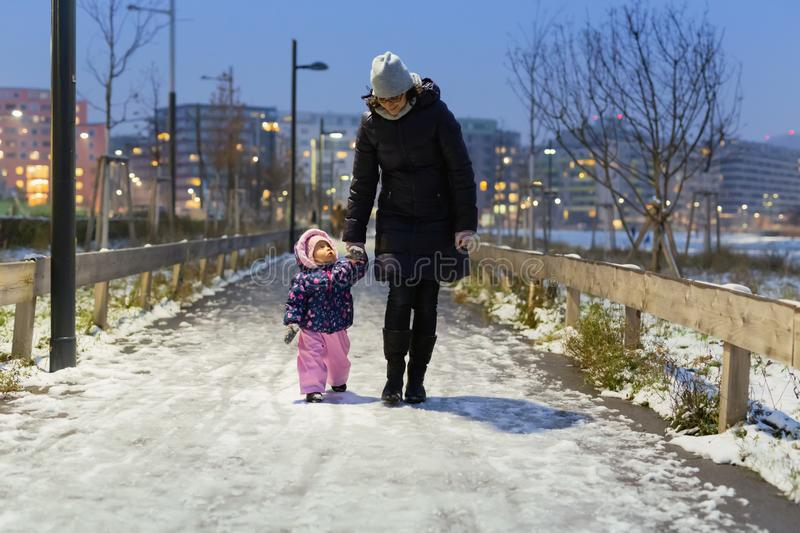 Mother and her small child walking in the snowy park in winter royalty free stock photography