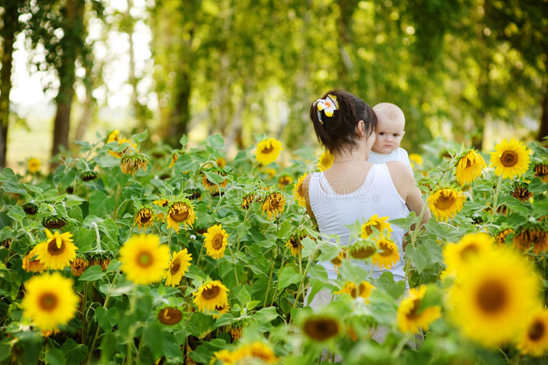 Mother and her son in the field of sunflowers royalty free stock photo