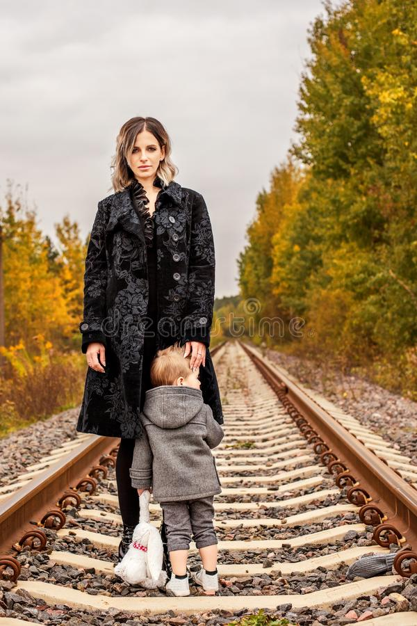Mother with her son on the forest railway tracks a sense of oppression and danger. Family mother with her son on the forest railway tracks a sense of oppression stock photo