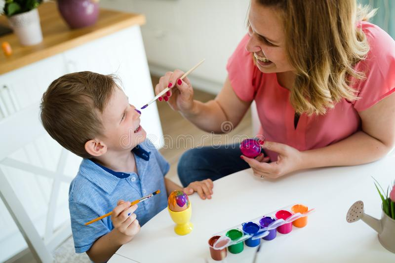 Mother and her son having fun decorate eggs stock images