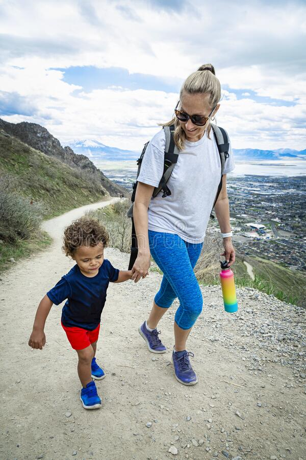 Mother and her son hiking up a scenic mountain trail together royalty free stock photos