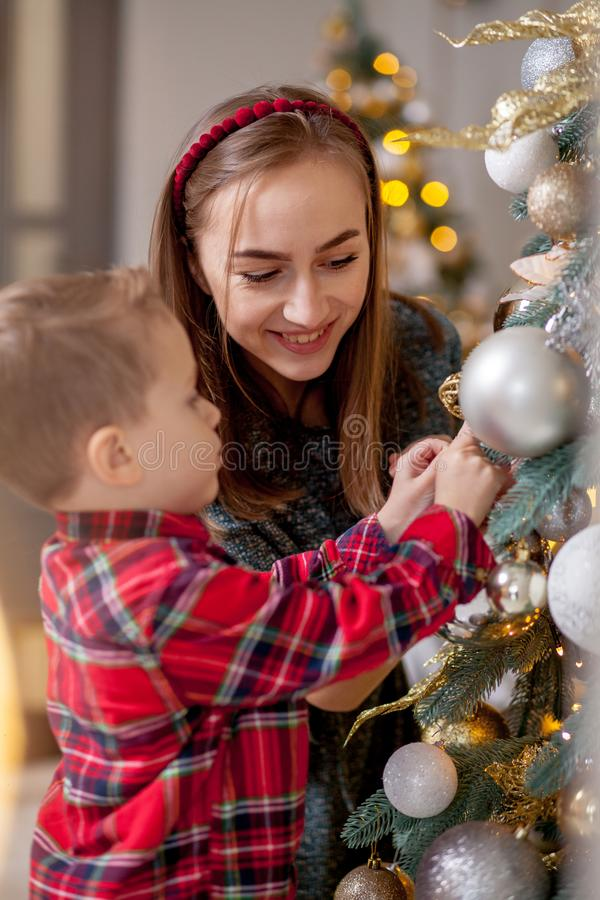 Mother and her son are at home decorated for Christmas. Family miracle time. Merry Christmas and Happy New Year royalty free stock photography