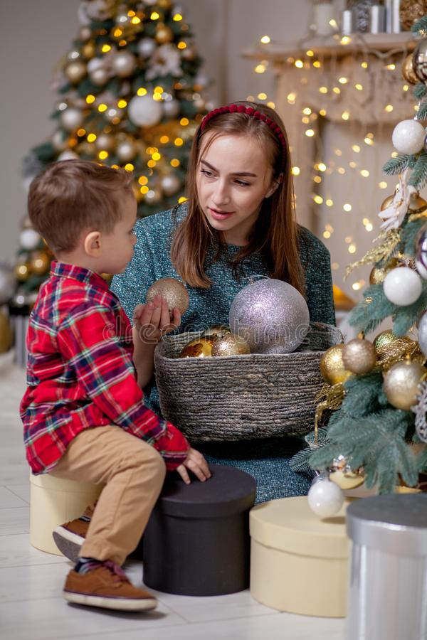 Mother and her son are at home decorated for Christmas. Family miracle time. Merry Christmas and Happy New Year royalty free stock photos