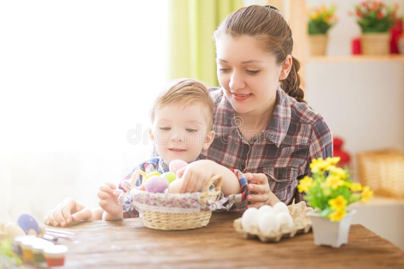 Mother and her son painting colorful easter eggs. Family celebrating Easter. Parent and child play indoors stock photos