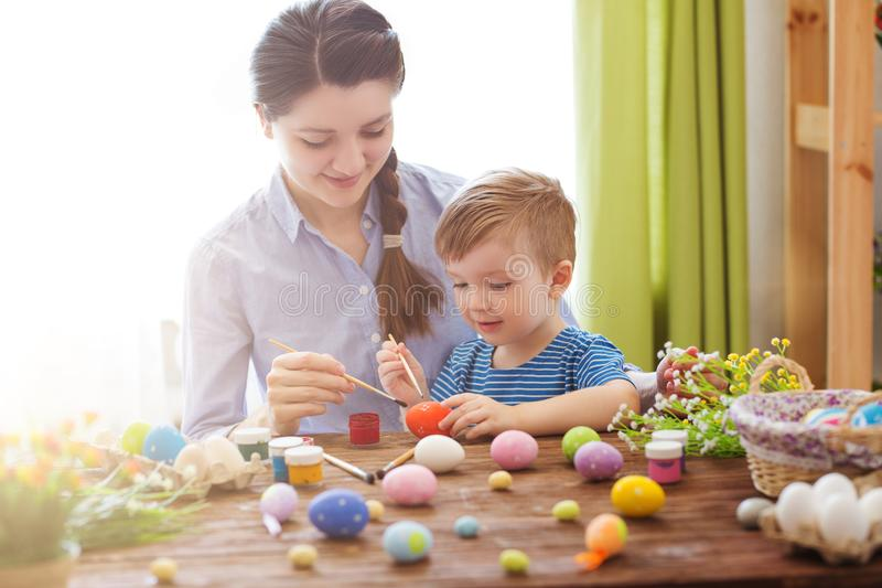 Mother and her son painting colorful easter eggs. Family celebrating Easter. Parent and child play indoors stock image
