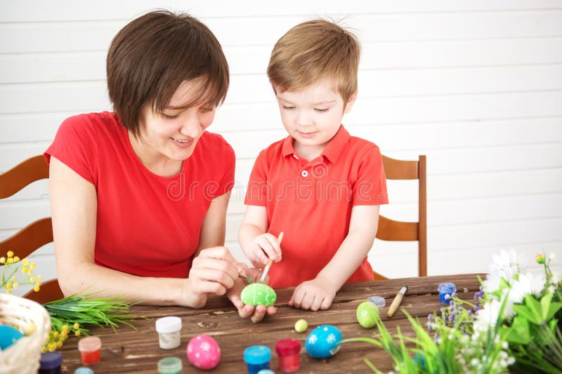 Mother and her son painting colorful Easter eggs. Happy family Mom and children son paint easter eggs with colors. Preparation for stock images