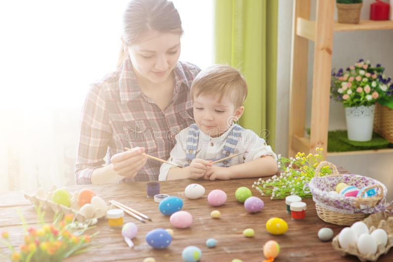 Mother and her son painting colorful Easter eggs. Happy family Mom and children son paint easter eggs with colors. Preparation for stock photography