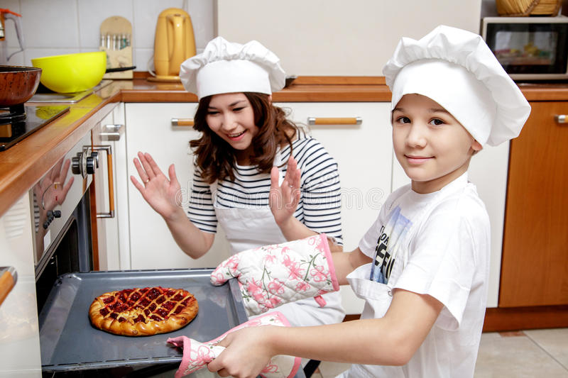 Mother and her son in white chef hats preparing a cake in the kitchen. stock photography