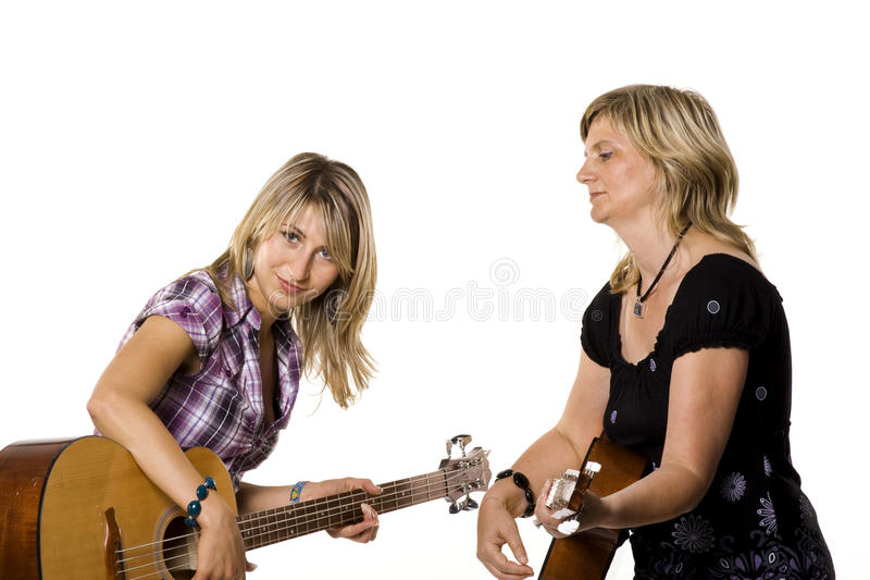 Mother And Her Teen Daughter Playing Guitar Royalty Free Stock Photos