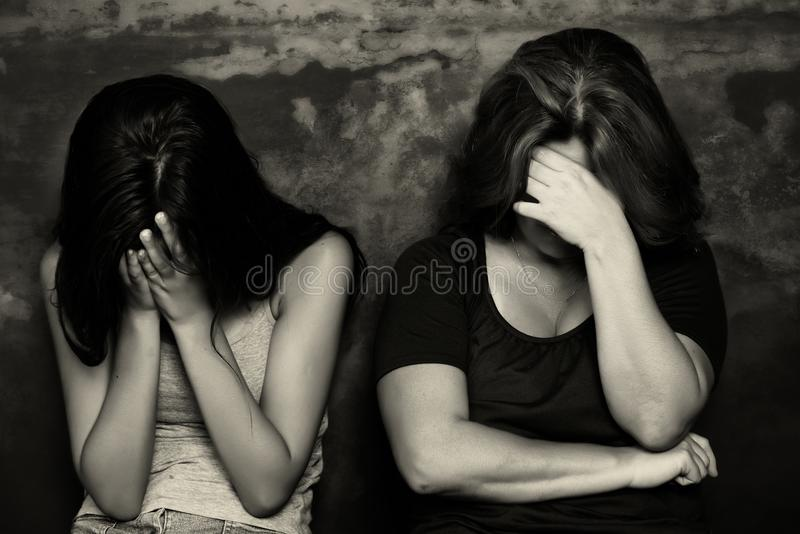 Mother and her teenage daughter crying stock photo
