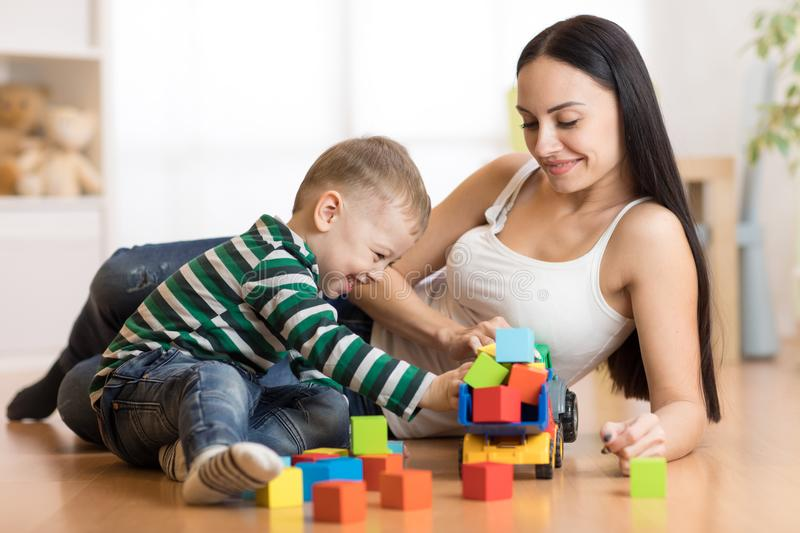 Mother and her toddler son plays with car in their living room stock image