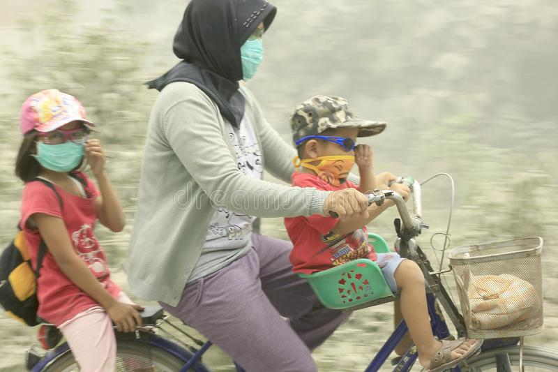 Mother with her two children through a volcanic ash eruption mount Kelud royalty free stock images