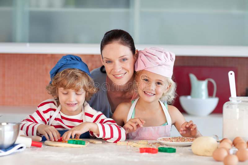 Mother with her Two Kids looking in the kitchen royalty free stock photo