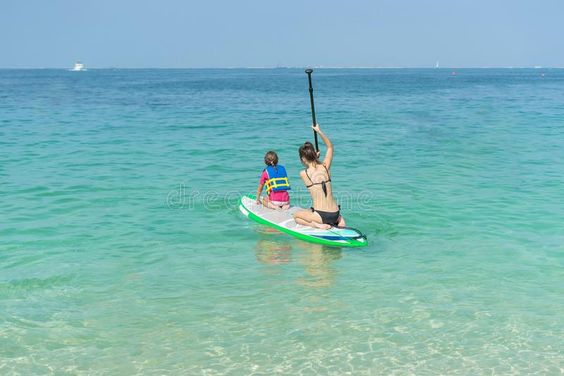 Mother and his adorable little daughter sitting on stand up board having fun during summer beach vacation stock photos