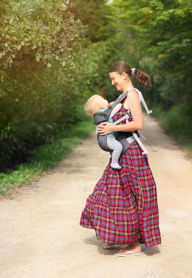 Mother with his infant son in baby carrier have fun outdoor. Hap royalty free stock photo