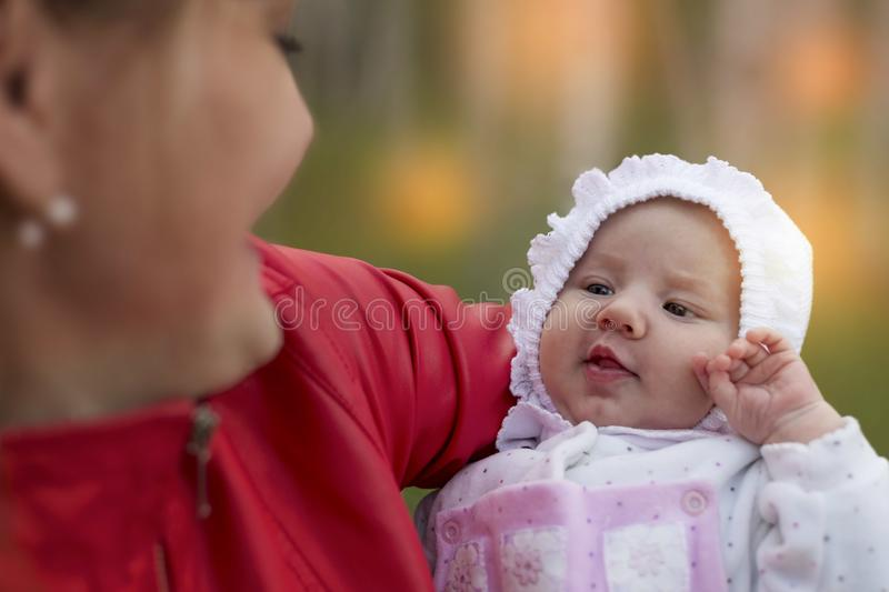 Mother hold baby in hands. Baby look at mother. Image of adorable baby on the mothers hands royalty free stock photos