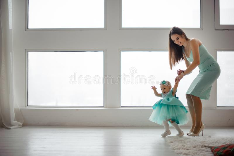 Mother hold daughter hand supporting her walking in the room stock images