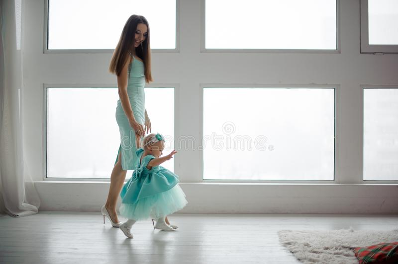 Mother hold daughter hand and walking in the room stock photos