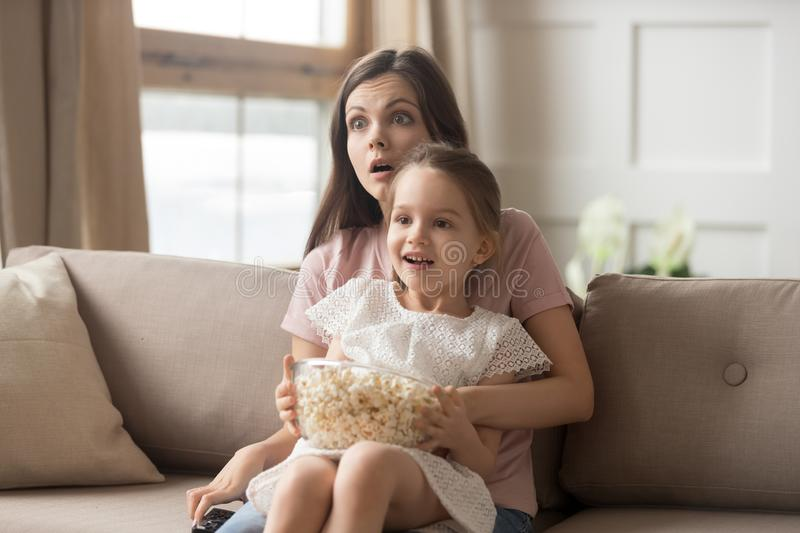 Mother hold daughter on lap watching movie feels shocked. Family sitting on sofa in living room mother holds on lap little daughter watching movie eating pop royalty free stock photo