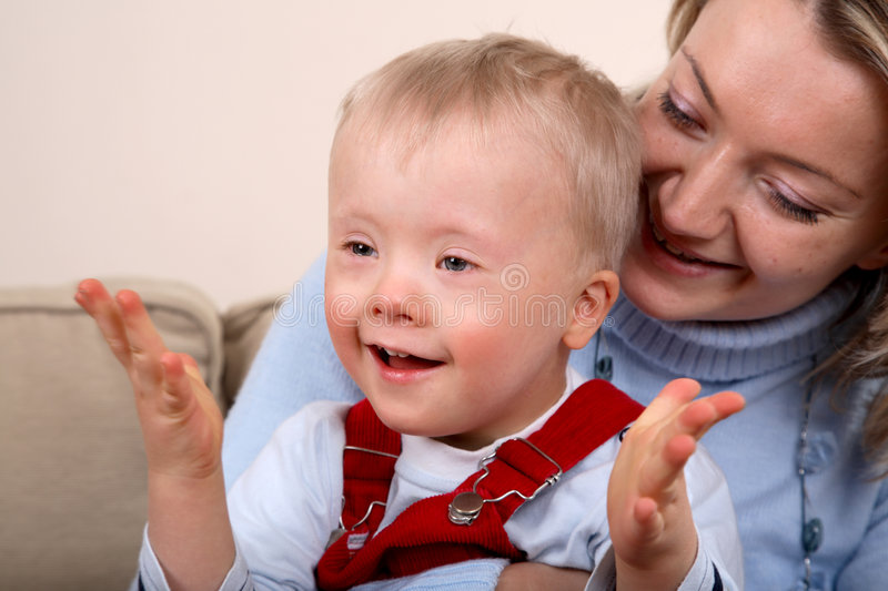 Mother hold handicapped boy stock image