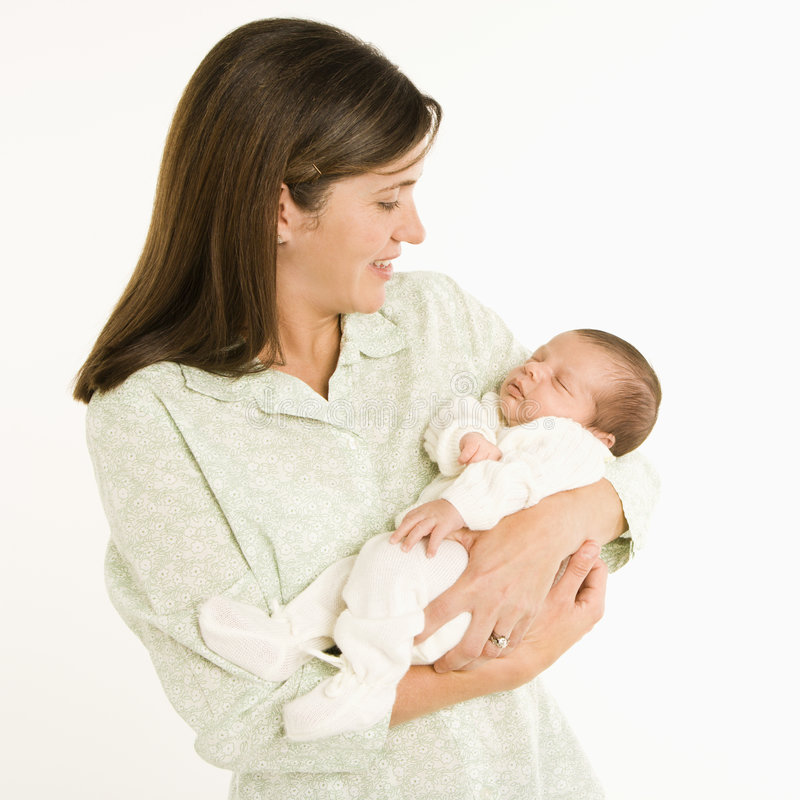 Mother holding baby. Mother holding baby smiling against white background royalty free stock images