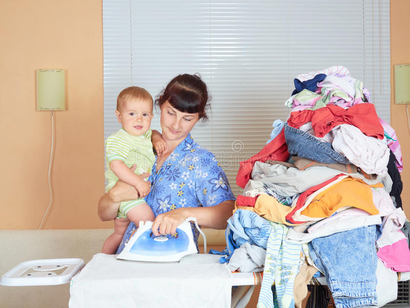 Mother holding baby in arm, ironing with the other arm. stock photos